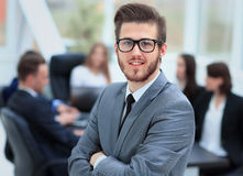 Successful business man standing with his staff in background at office Royalty Free Stock Photo