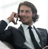 Business man talking on a smartphone while sitting in a comfortable chair. Successful business man talking on a smartphone while sitting in a comfortable chair Royalty Free Stock Photo