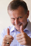 Successful business man with thumbs up. Looking at camera. Vertical composition stock photo