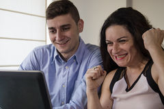 Successful business man and woman smiling, looking at laptop screen at home office Stock Image