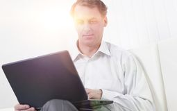 Successful business man working on laptop sitting on sofa royalty free stock images
