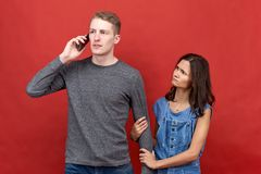 Successful business man talking on the phone for very important matters. His beautiful girlfriend hurt and unhappy. stock photography