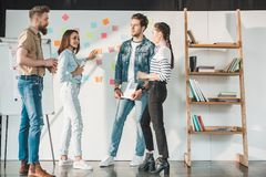 Successful business people discussing ideas by white board with sticky notes in modern. Light office stock photos
