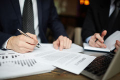 Successful Business People Signing Contract. Closeup portrait of two unrecognizable business people wearing black formal suits signing contract papers at table Royalty Free Stock Image