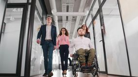 A successful business people walking through the corridor in the office centre. A man in a wheelchair royalty free stock image