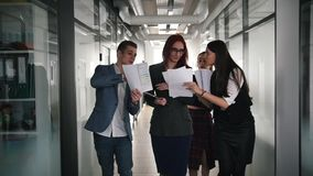 A successful business people walking through the corridor. People showing the documents to their woman chief stock footage