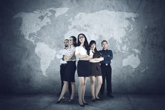 Successful business people with world map. Group of successful multiracial business people with female leader at front, standing in front of world map background Stock Photo