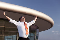 Successful business person raising hands. Successful businessman in white shirt, orange tie and sunglasses raising his hands and screaming in front of office Royalty Free Stock Image