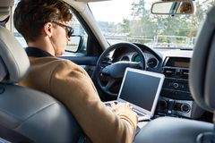 Successful Business Person Using Laptop in Car. Back view portrait of successful modern entrepreneur wearing sunglasses working, using laptop sitting in luxury Stock Photos