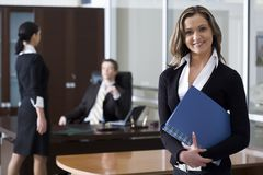 Successful business plan. Pretty businesswoman holding the document case in the office with two another persons on the background Royalty Free Stock Photography