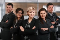 Successful business team. Team of successful happy businesspeople standing in office, businesswoman in front smiling Royalty Free Stock Photos