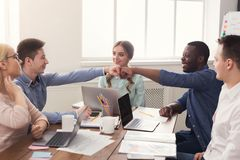 Successful business team bumping fists. Cheerful business multiethnic team bumping fists, celebrating successful project, cooperation and teambuilding concept Stock Photo