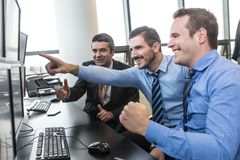 Successful business team celebrates business success in modern corporate trading office. royalty free stock photo