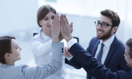 Successful business team giving each other a high-five, standing in the office. Concept of success Stock Images