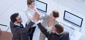Successful business team giving each other a high-five, standing in the office. Concept of success stock image