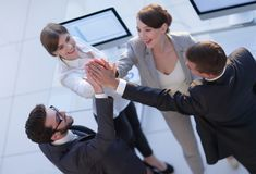 Successful business team giving each other a high-five, standing in the office. Concept of success royalty free stock photography