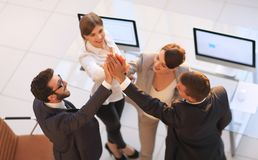 Successful business team giving each other a high-five, standing in the office. Concept of success royalty free stock images