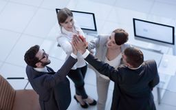 Successful business team giving each other a high-five, standing in the office. Concept of success royalty free stock photo