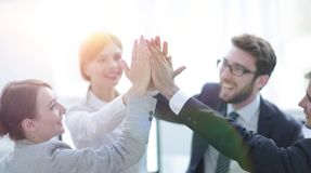 Successful business team giving each other a high-five, standing in the office. Concept of success stock photography