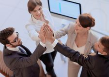 Successful business team giving each other a high-five, standing in the office. Concept of success Stock Photos