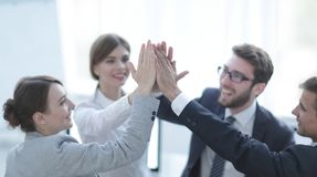 Successful business team giving each other a high-five, standing in the office. Concept of success stock photo