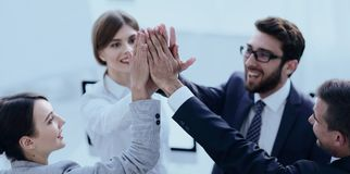 Successful business team giving each other a high-five, standing. In the office.concept of success Royalty Free Stock Photography