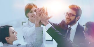 Successful business team giving each other a high-five, standing stock photo