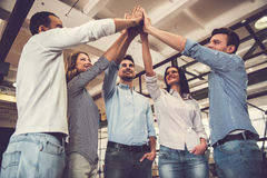 Successful business team. Is giving high five and smiling while standing in office Royalty Free Stock Photos