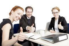 Successful business team giving a thumbs up. Successful business team sitting around an office table having a meeting smiling and giving a thumbs up of Royalty Free Stock Photos