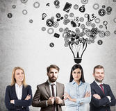 Successful business team ideas. Successful business team members are standing near a concrete wall with a light bulb with smaller icons drawn above them Royalty Free Stock Image