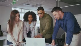 Happy young multi ethnic business team working together in teamwork on computer at office desk stock footage