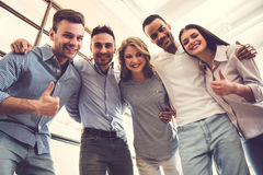 Successful business team. Is showing thumbs, looking at camera and smiling while standing in office Stock Photos