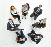 Successful business team sitting in a circle. View from the top.successful business team sitting in a circle and looking at the camera Royalty Free Stock Photo