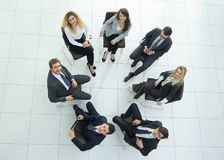 Successful business team sitting in a circle. View from the top.successful business team sitting in a circle and looking at the camera Royalty Free Stock Images