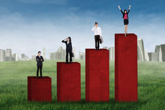 Successful business team standing on chart Stock Images
