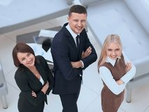 Successful business team standing in office and looking at camera. Stock Images