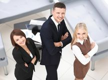 Successful business team standing in office and looking at camera. Royalty Free Stock Photos