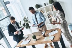 Successful business team. Top view of young modern people in smart casual wear discussing business while standing in the creative office stock images