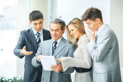 Successful business team with tablet and documents discussing business matters Stock Photos