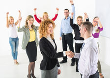 Successful Business team. Two successful business people shaking hands at the meeting. Group their colleague celebrating in the background stock images
