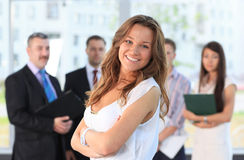 Successful business woman. Successful business women standing with her staff in background at office Stock Photos