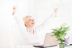 Successful Business woman. Cheerful Business woman sitting in the office with raising hands Royalty Free Stock Photo