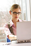 Successful business woman. A successful business woman is working on a table with a laptop Royalty Free Stock Photos