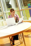 Successful business woman. A successful business woman is working on a table with a laptop with documents Stock Photo