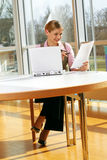 Successful business woman. A successful business woman is working on a table with a laptop with documents Stock Images