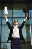Successful business woman with arms up and documents. Royalty Free Stock Photo