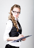 Successful business woman in a business suit and glasses holding folder Royalty Free Stock Photo