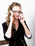 Successful business woman in a business suit one hand corrects glasses Royalty Free Stock Photos