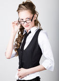 Successful business woman in a business suit one hand corrects glasses Stock Images