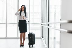 Successful business woman with coffee and suitcase in an office setting Royalty Free Stock Photos
